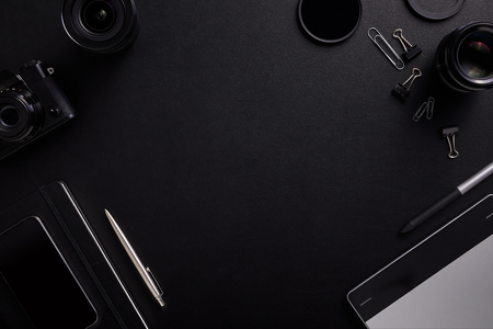 Top view of the black table graphic designer with camera, lenses and diary with copy space. Flat lay shot
