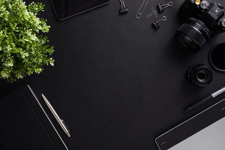 Top view of the table graphic designer with camera, lenses and diary with copy space. Flat lay shot on black background