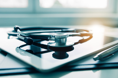Tablet and stethoscope on white table. Medicine and modern technology concept