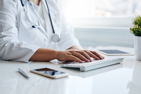Female doctor works with computer in the office