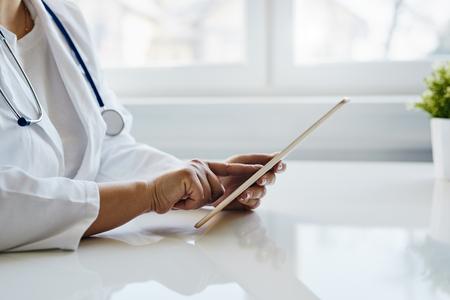 Female doctor working on a digital tablet near a window