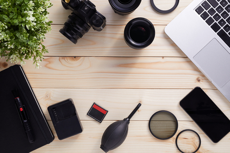 Top view of photographer desk with latptop, camera, lenses and accessories with copy space. Flat lay shot on wooden background.