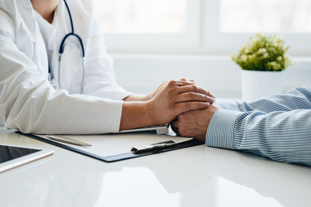 Friendly female doctor reassuring the patient and holding his hands in the office. Reklamní fotografie