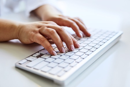 Doctora escribiendo en el teclado del ordenador en la oficina Foto de archivo