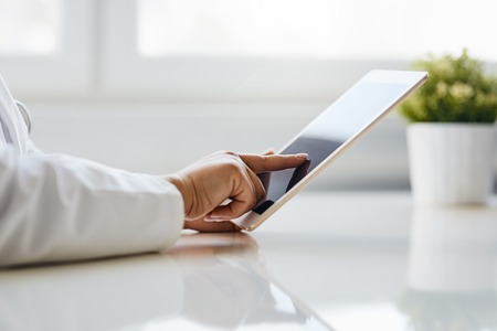 Female doctor uses tablet while sitting in medical office