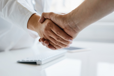 Female doctor shakes hands with his patient in the office