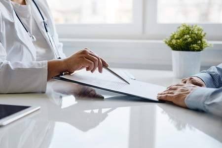 Female doctor recommends to fill in a medical document in the office.