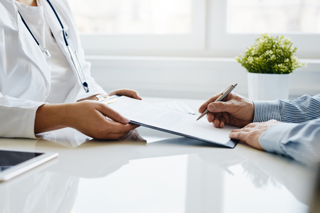 Patient signs a medical report with his doctor in the office