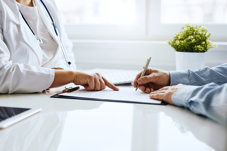 Patient signs a document with his doctor in medical office Stock Photo