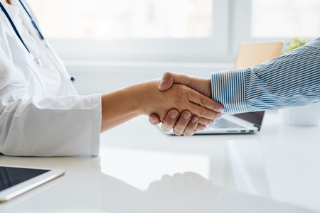 Female doctor shakes hands with his patient in medical office