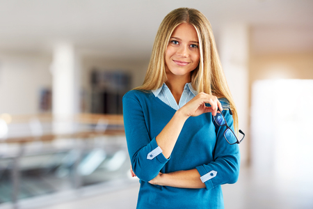 Young woman with glasses in a business center on the corridor
