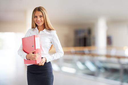 Smiling woman in business center with folder in hands Reklamní fotografie