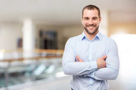 Smiling businessman stands in the business center with crossed arms Reklamní fotografie