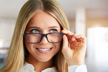 Portrait of happy woman with glasses in business center