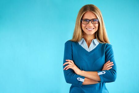 Happy business woman with crossed hands on blue background