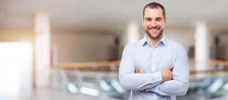 Happy man in the business center with crossed arms