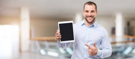 Happy man in the business center with tablet Reklamní fotografie