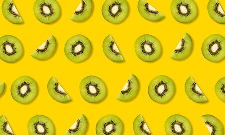 Top view of fruit pattern from slices of kiwi on yellow background Stock Photo