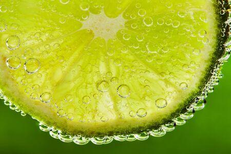 Nahaufnahme von Wasser mit Limettenscheibe und Blasen