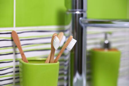 Four bamboo toothbrushes in green glass in bathroom