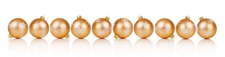 Golden Christmas ornaments in a row on white background with reflection Stock Photo