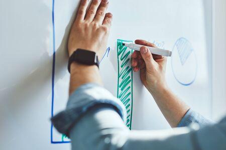 El hombre dibuja un gráfico con un marcador en la pizarra en la oficina