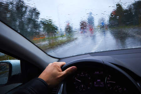 A man drives a car under a heavy drizzle, autumn weather