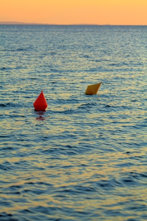 Red and yellow buoys during sunset photo