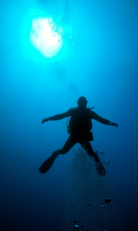 Silhouette of diver with sun disk behind photo