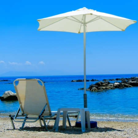 Sun Lounger and Parasol on a Beach photo
