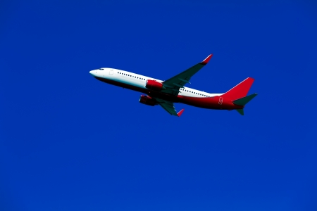 Red and White Airplane in sky photo