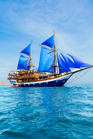 sailing boat: Vintage Wooden Ship with Blue Sails near Komodo Island, Indonesia