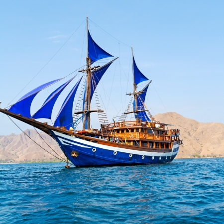 schooner: Vintage Wooden Ship with Blue Sails near Komodo Island, Indonesia