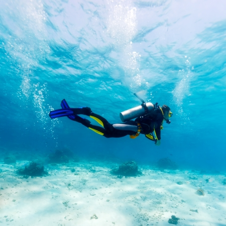 물 표면과 바다의 바닥 사이의 젊은 남자 스쿠버 다이버의 실루엣