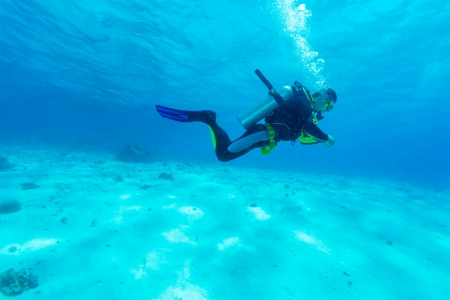 underwater life: Silhouette of Young Man Scuba Diver between Water Surface and Sea Bottom Stock Photo