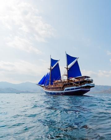 komodo: Vintage Nave in legno con vele blu vicino a Isola di Komodo, Indonesia