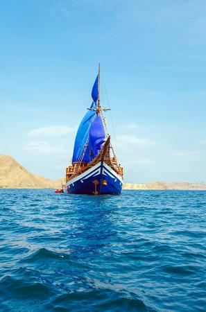 komodo island: Vintage Wooden Ship with Blue Sails near Komodo Island, Indonesia