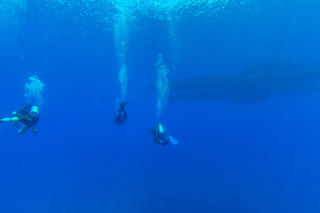 divers: Group of Divers near Boat Swimming Underwater