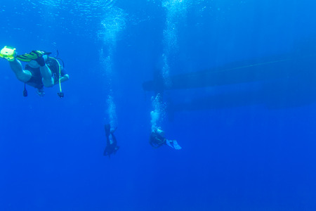 aqualung: Group of Divers near Boat Swimming Underwater