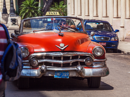 cabriolet: HAVANA, CUBA - APRIL 1, 2012: Orange Cadillac Series 62 taxi cabriolet
