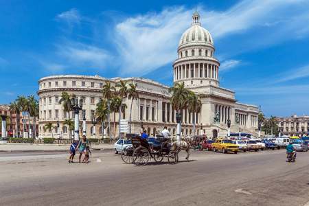 HAVANA, CUBA - APRIL 1, 2012: Heavy traffic with horse carriages, motorbikes and vintage cars in front of Capitolio
