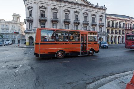 capitolio: HAVANA, CUBA - APRIL 2, 2012: Orange school bus in front of Capitolio Editorial