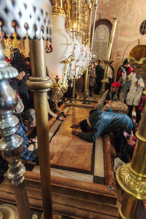 JERUSALEM, ISRAEL - FEBRUARY 16, 2013: Pilgrims praying near Stone of Unction at entrance in Church of the Holy Sepulchre