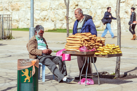 street market: JERUSALEM, ISRAEL - FEBRUARY 20, 2013: Bread street vendor chatting with friend on the streets of old city