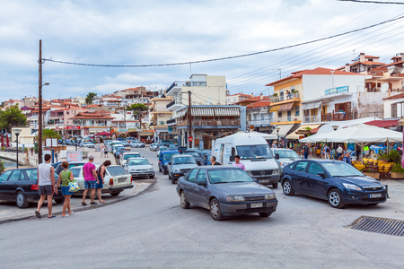 seson: NEOS MARMARAS, GREECE - JUNE 13, 2009: Busy traffic with autos and tourists at peak of seson Editorial