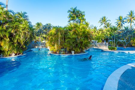 BALI, INDONESIA - AUGUST 29, 2008: Tourists swimming in enormous exotic pool with palm tree islands