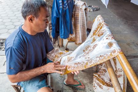 YOGYAKARTA, INDONESIA - AUGUST 28, 2008: Man painting wax at traditional batik factory