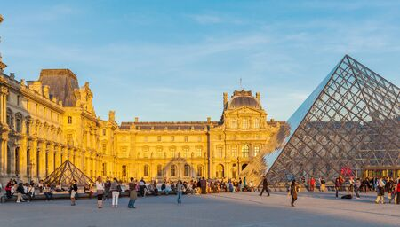 louvre pyramid: PARIS, FRANCE - APRIL 6, 2011: People have a rest in front of the Louvre Palace and Pyramid, sunset view