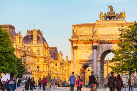 PARIS, FRANCE - APRIL 6, 2011: People walking in front of Arc de Triomphe and Louvre Palace, sunset view