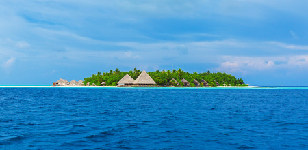 Small atoll island with traditional wooden bungalows and Indian ocean, Maldives